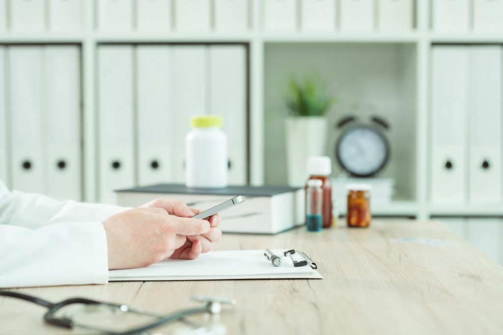 Doctor using smartphone in medical office